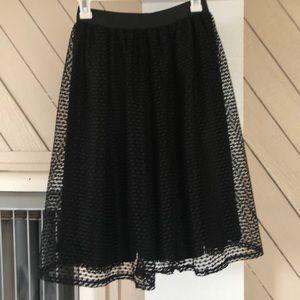 Midi/ knee length black skirt with mesh overlay.